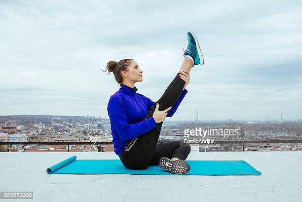 young pretty woman exercising on the rooftop
