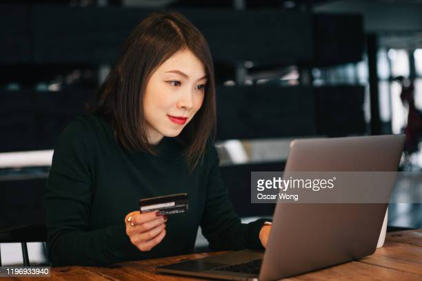 young pretty woman using laptop for online shopping on a wooden table at cafe - addiction stock pictures, royalty-free photos & images