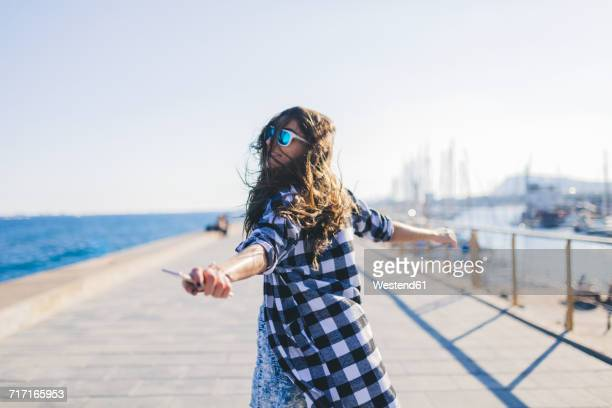Young pretty woman wearing beach wear wlaking by the sea