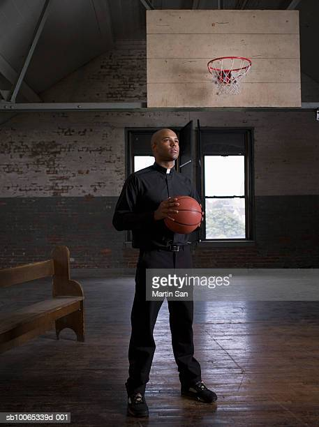 Young priest standing in court holding basketball, looking away