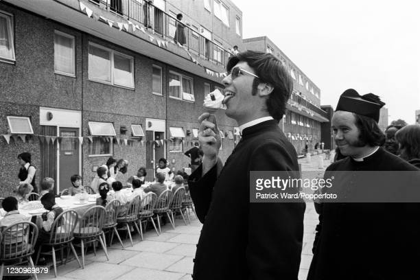 Young priests, one licking an ice cream cone, observing a children's party during Deptford Carnival Week in East London, England, circa 1975. This...