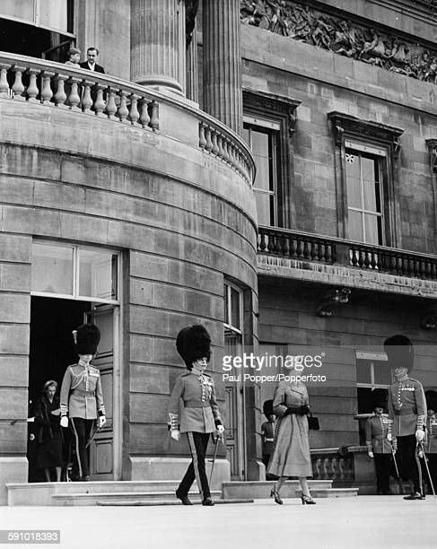 Young Prince Charles leans over the balcony to watch his mother Queen Elizabeth II walk with officers of the Grenadier Guards to take her position on...