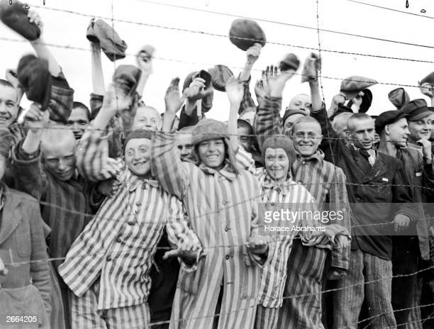 Young prisoners interned at Dachau concentration camp cheering their liberators the 42nd Division of the US Army The boy second from left has been...