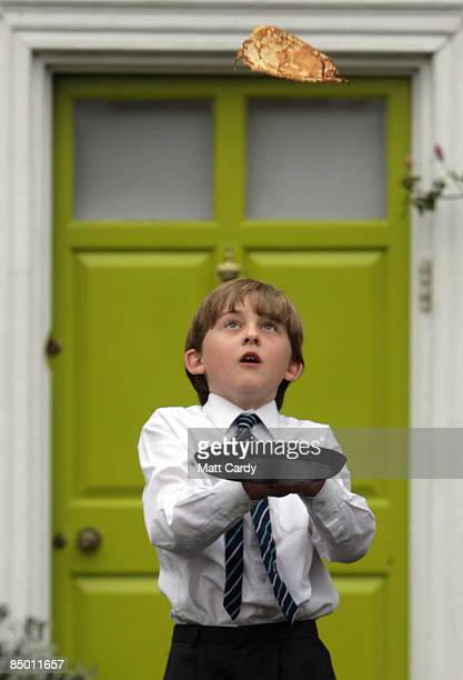 A young probationer a trainee chorister of Salisbury Cathedral Choir flips a pancake to mark Shrove Tuesday outside the Canon Precentor house close...