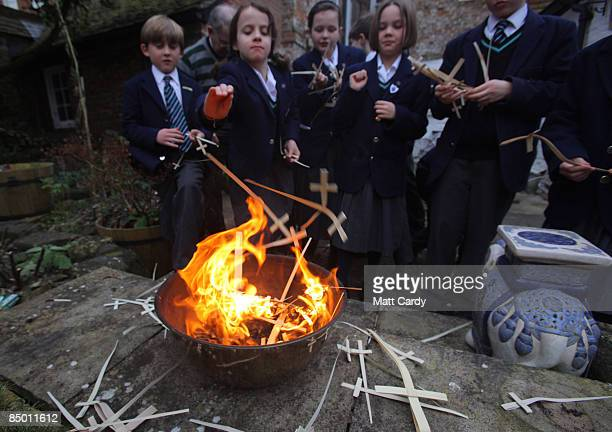 Young probationers trainee choristers at Salisbury Cathedral Choir burn last year's Palm Sunday crosses to mark Shrove Tuesday and create ash that...