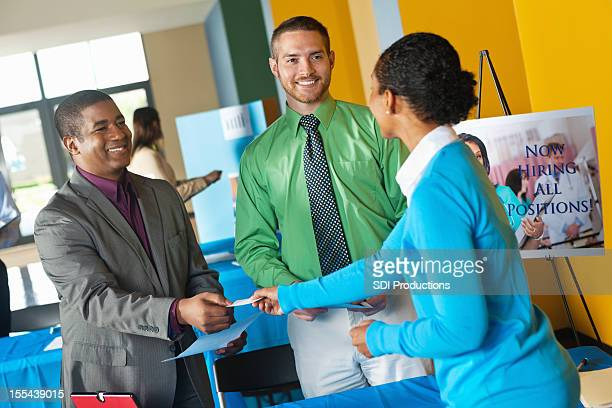 Young professional accepting business card from team at job fair