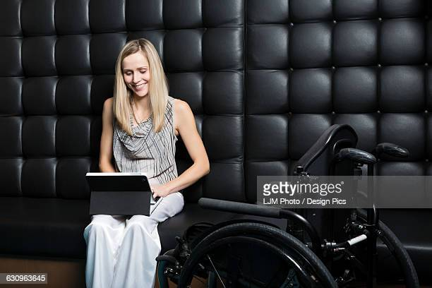 young professional business woman who is a paraplegic working on her computer - paraplegic woman stock photos and pictures