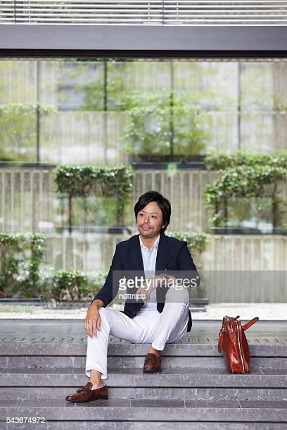 Young professional businessman sitting on the steps