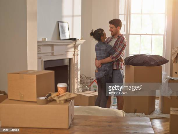 A young professional couple hugging in new home