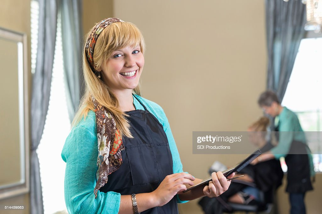 young professional hairstylist using digital tablet in upscale salon stock photo - Professional Hairstylist