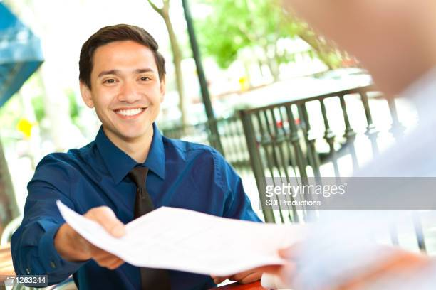 Young professional handing document to colleague at outdoor cafe