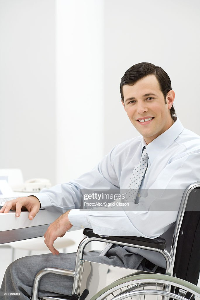 Young professional in wheelchair, smiling at camera : Stock Photo