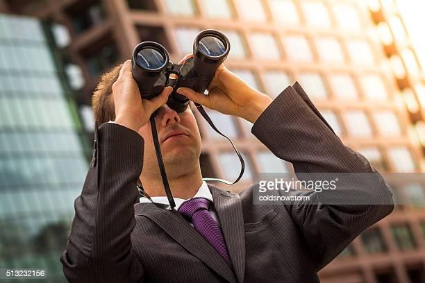 Profesional joven mirando a través de binoculares en el distrito de negocios, Londres, Reino Unido