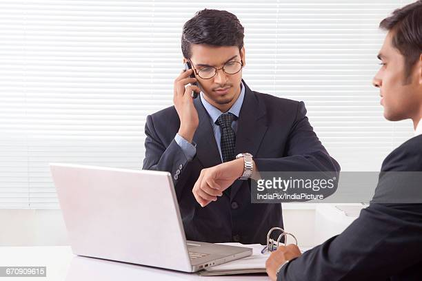 Young professional man looking at wrist watch while talking over mobile phone at office while another professional man is sitting opposite to him