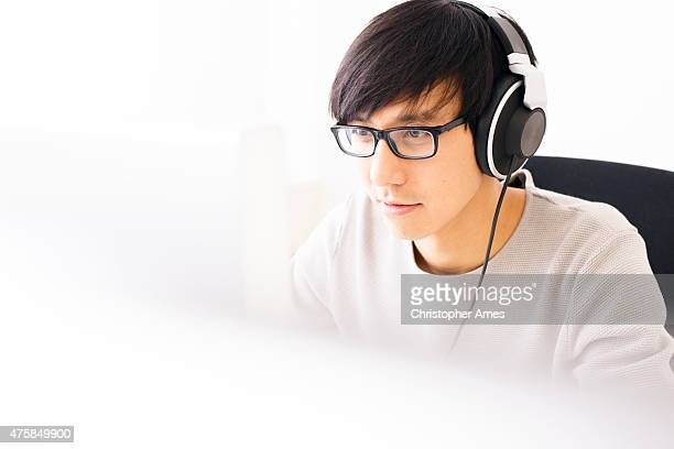 Young Professional Man Wearing Headphones Concentrating on Computer Screen