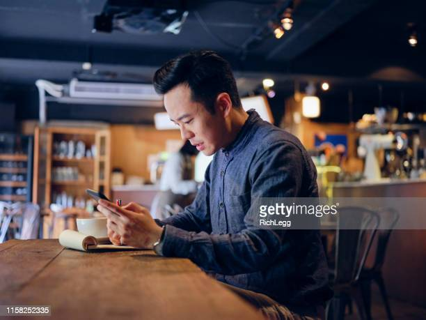 young professional man working in a small coffee shop - asia stock pictures, royalty-free photos & images