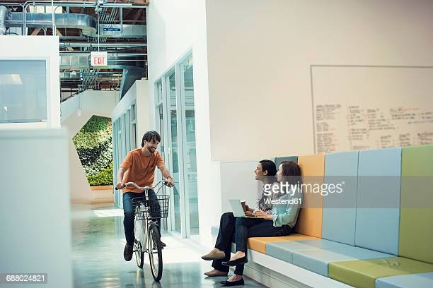 Young professional on bicycle meeting colleagues in lobby