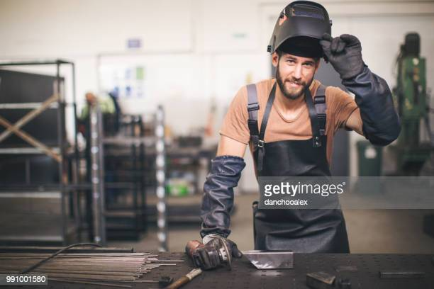 Young professional welder grinding and welding metal bars