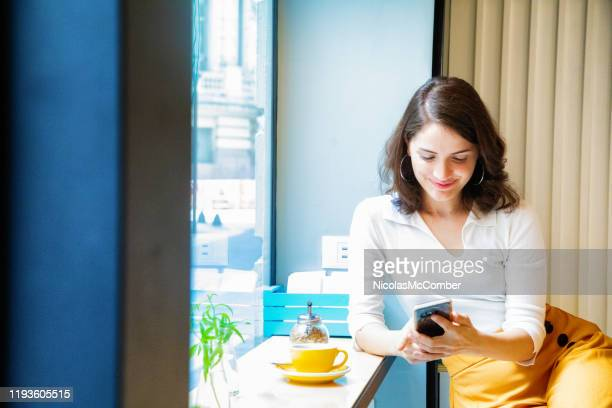 young professional woman enjoying a coffee by window with her mobile phone - phone message stock pictures, royalty-free photos & images