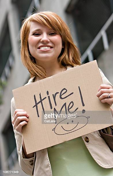 young professional woman holding hire me sign - paperboard stock photos and pictures
