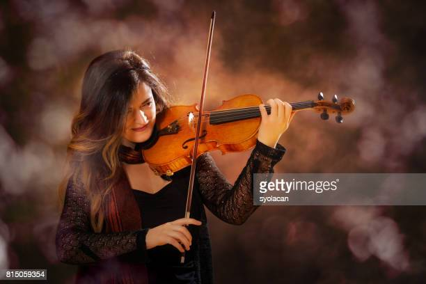 Young professional woman violinist during performance