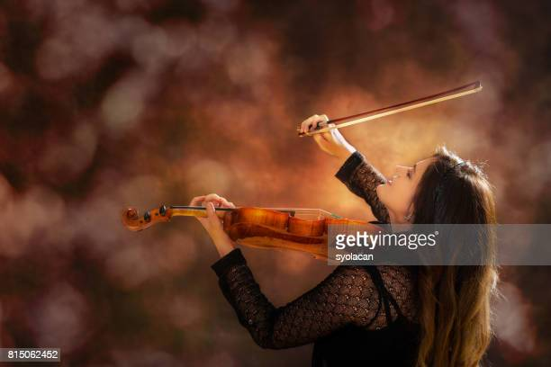 Young professional woman violinist during powerful stage performance