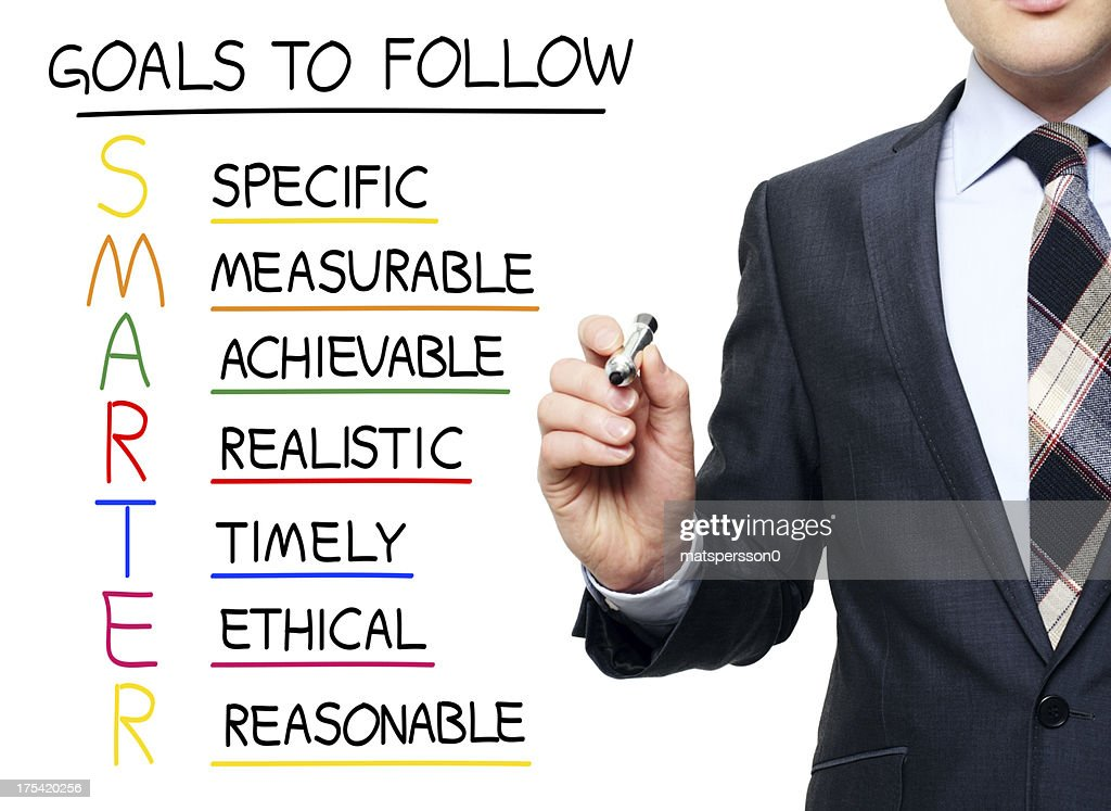 Young professional writing acronym for SMARTER : Stock Photo