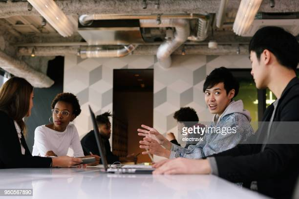 young professionals at coworking space - coworking stock photos and pictures