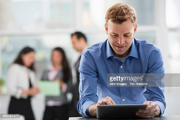 Young professionals at work. A man in an open necked shirt using a digital tablet. A group of men and women in the background.