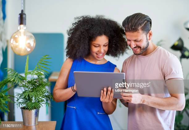 young professionals looking at ipad in eco friendly modern office - sleeveless dress stock pictures, royalty-free photos & images