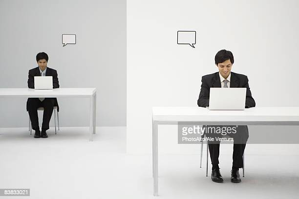 Young professionals sitting at desks, using laptops, blank word bubbles over their heads