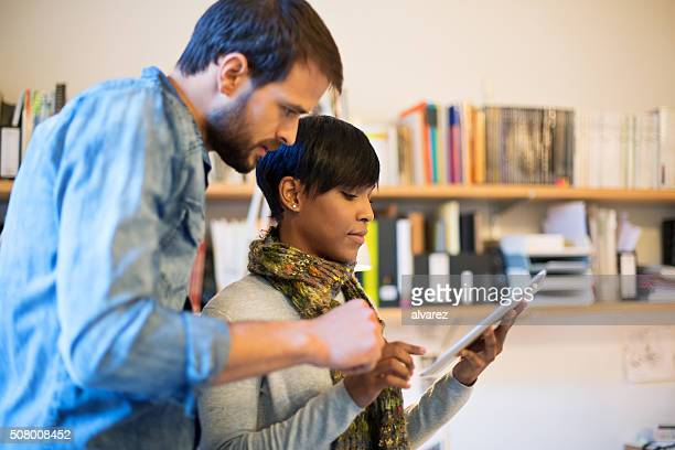 Young professionals using digital tablet at startup