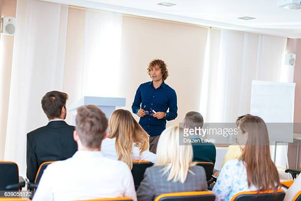 Young professor talking on seminar in conference hall