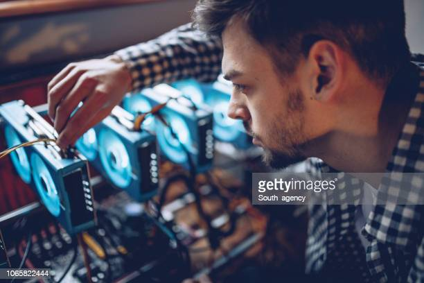 young programmer preparing mining rig - cryptocurrency mining stock pictures, royalty-free photos & images