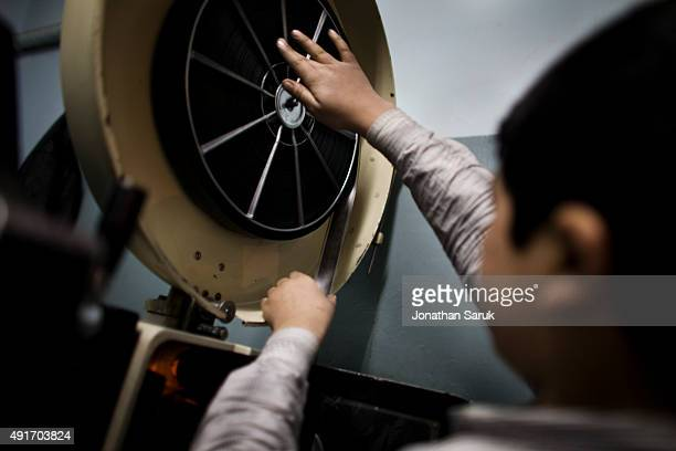 A young projectionist fixes a film real at Pamir Cinema November 27 2010 in Kabul Afghanistan Going to the movies once banned under the Taliban has...