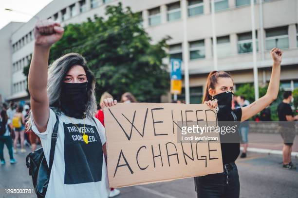 """young protestant women holding a poster with text """"we need a change"""" - campaigner stock pictures, royalty-free photos & images"""