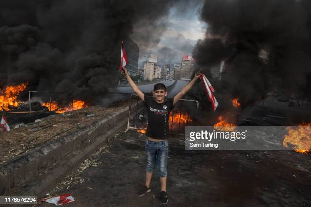 Young protester gestures in front of a burning barricade in Beirut, Lebanon during unrest sparked by economic difficulties on October 18, 2019....