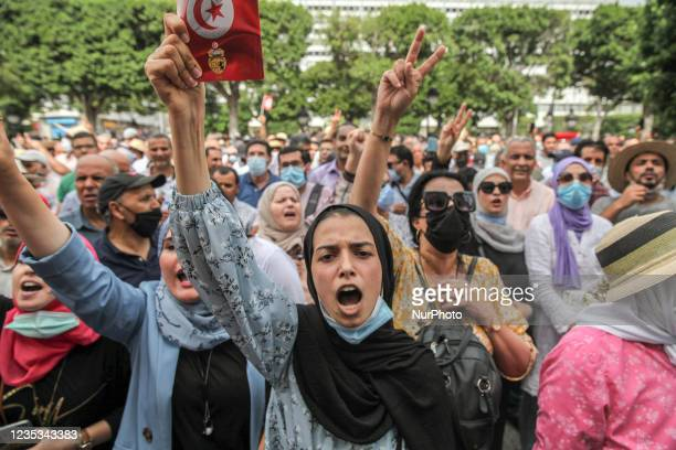 Young protester lifts a copy of the Tunisian constitution as she shouts slogans, while others make victory sign , during a demonstration held in the...