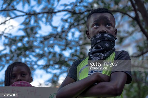 A young protester listens while Stephen Jackson former NBA player speaks outside the Hennepin county Government Center during a Justice for George...