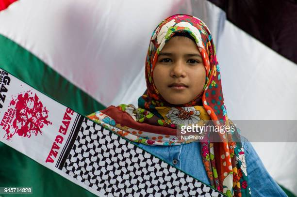 A young protester pictured in front of a Palestinian flag during a rally to commemorate Palestinian Land Day at outside of the US embassy in Kuala...