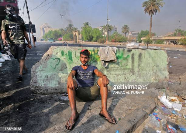 A young protester rests behind a concrete barricade during clashes with riot police amidst demonstrations against state corruption failing public...