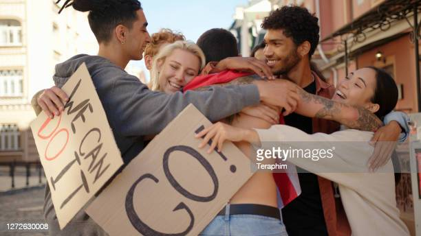 young protester with usa flag walks to multiracial activists and hugging them. mass protest concept - participant stock pictures, royalty-free photos & images