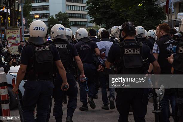 Young protesters is walked away handcuffed and surrounded by the riot policemen who just apprehended him.