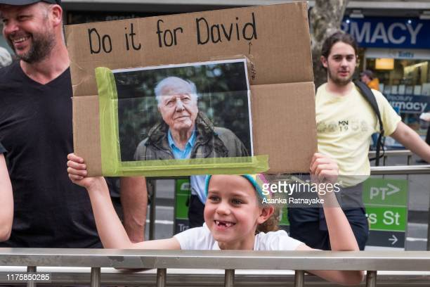 Young protestor holding a placard with a picture of broadcaster David Attenborough on September 20, 2019 in Melbourne, Australia. Rallies held across...