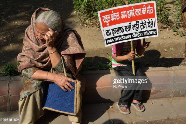 A young protestor sits holding a placard demanding justice from Indian National Congress Party President Rahul Gandhi along Akbar Road in New Delhi...