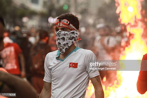 CONTENT] Young protestor with a Turkish flag in his tshirt in front of a fire barricade in Osmanbey area near Taksim Square during the riots at...