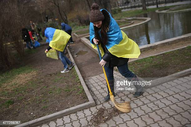 Young proUkrainian sympathizers draped in Ukrainian flags sweep a park clean in what they said was a symbolic action meant to express their love for...