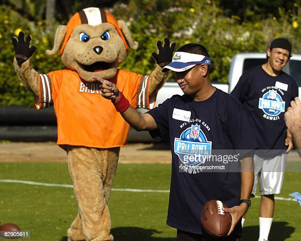 A young punter lines up a kick as the Cleveland Browns mascot watches during the Special Olympics February 8 2006 in Honolulu Hawaii
