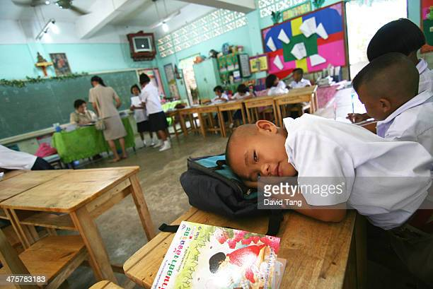 CONTENT] A young pupil rests his head while teachers are looking away