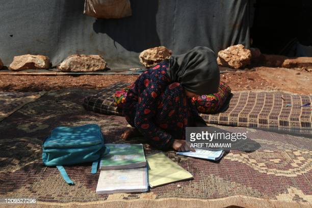 A young pupil studies in front of a tent in a camp for displaced Syrians in the village of Kafr Yahmoul in the northwestern Idlib province amid the...